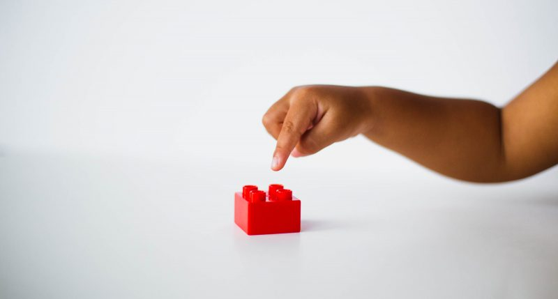 Child pointing to a lego block